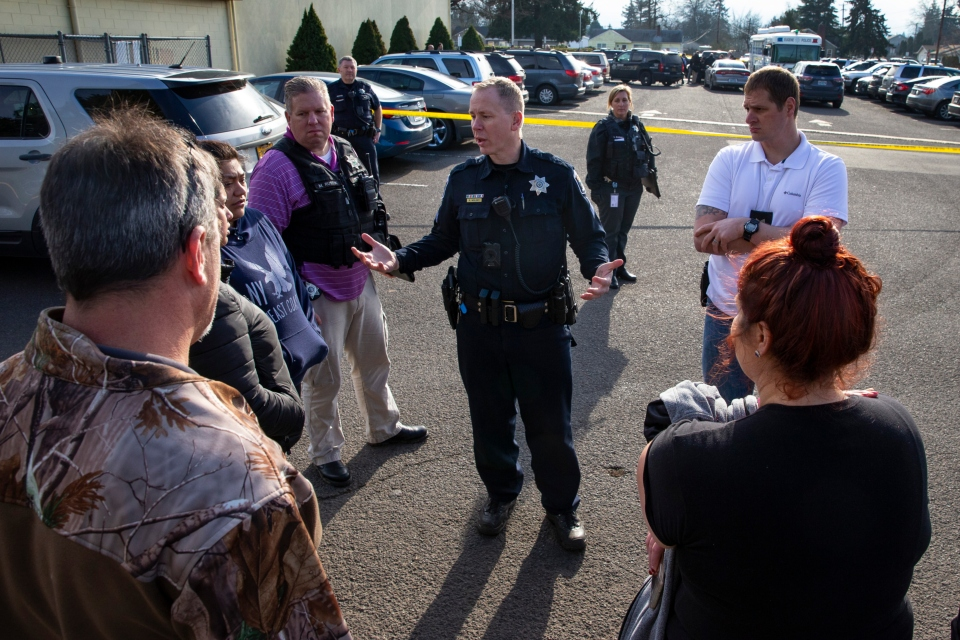 Eugene Police Sgt. Ryan Molony, center, talks to parents outside Cascade Middle School in Eugene, Ore. after a shooting, Friday Jan. 11, 2019. A suspect was shot Friday at an Oregon middle school, but no students or teachers were hurt, police said. (Chris Pietsch/The Register-Guard via AP)