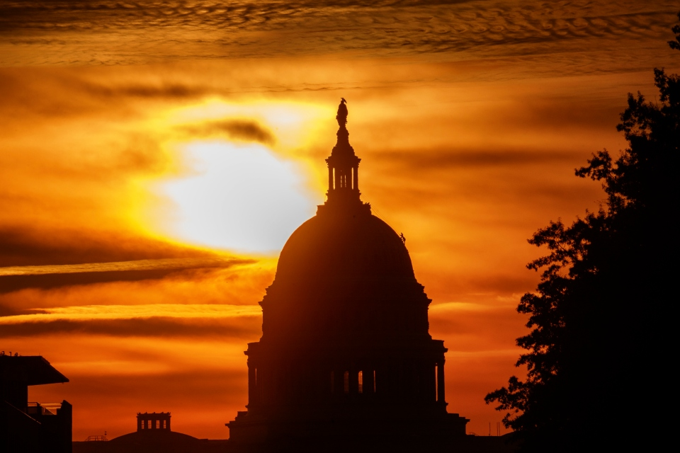 In this Oct. 26, 2018, file photo the rising sun silhouettes the U.S. Capitol dome at daybreak in Washington. A new government report says that the U.S. budget deficit is set to hit $897 billion this year and predicts that economic growth will slow as the effects of President Donald Trump's tax cut on business investment begin to drop off. (AP Photo/Alex Brandon, File)