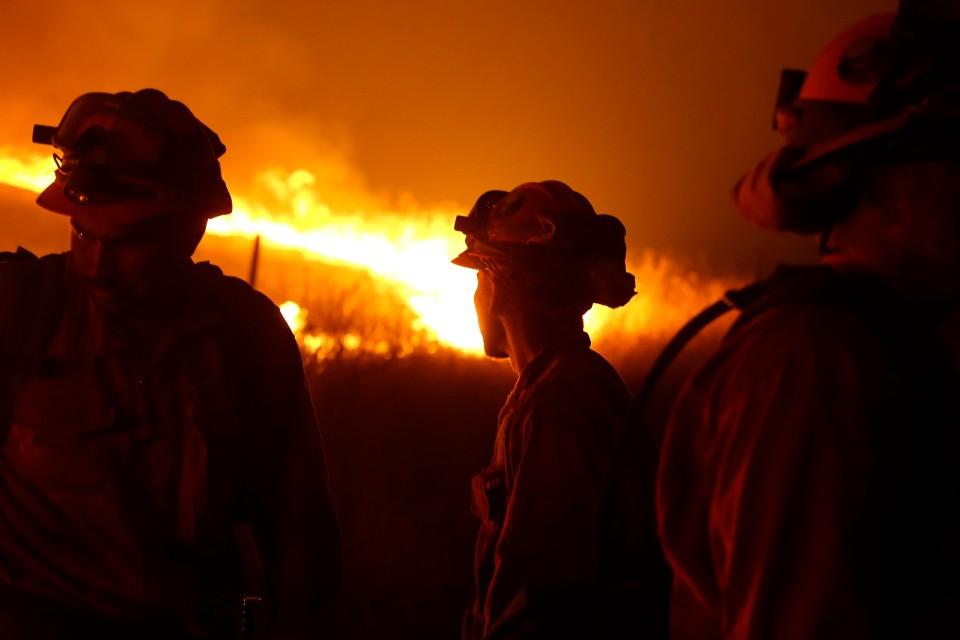 In this Sept. 12, 2015 file photo, California Department of Corrections and Rehabilitation inmates stand guard as flames from the Butte Fire approach a containment line near San Andreas, Calif. Attorneys representing 14 local governments said Tuesday, June 18, 2019 that they had reached a $1 billion settlement with California utility Pacific Gas & Electric for a series of fires dating to 2015. (AP Photo/Rich Pedroncelli, File)