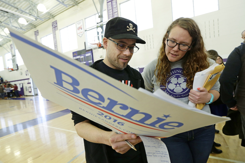 Stuart Huntoon, left, and Stephanie Edmisson, right, hold a sign supporting Democratic presidential candidate Sen. Bernie Sanders as they attend a precinct group during a Democratic caucus at Garfield High School in Seattle, March 26, 2016. Organizers for Sanders' 2020 campaign have updated their efforts in Washington, one of a growing number of states switching from caucuses to primary elections for selecting presidential candidates. (AP Photo/Ted S. Warren, File)