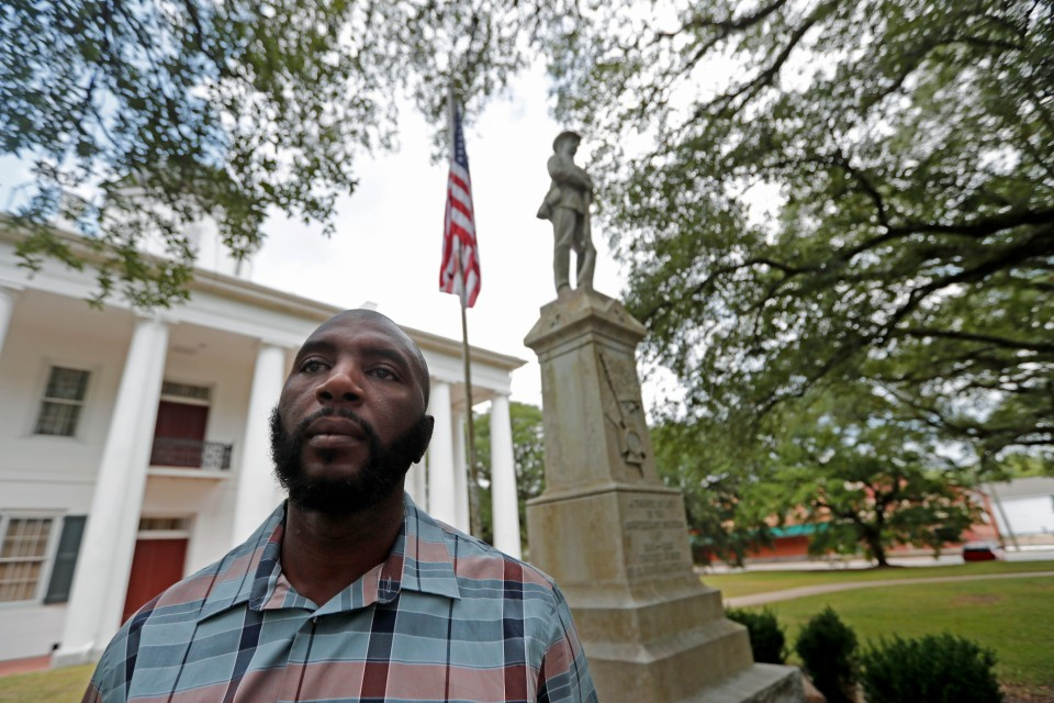 "FILE - In this Aug. 1, 2018 file photo, Ronnie Anderson poses for a photo in front of a confederate statue on the lawn of the East Feliciana Parish Courthouse in Clinton, La. Anderson is asking the state's Supreme Court to move his trial away from a courthouse with a Confederate statue at it. Anderson is facing a charge of illegal possession of a stolen firearm. His request, filed Monday, July 15, 2019, says the 30-foot-tall Confederate monument outside the East Feliciana Parish Courthouse is a ""symbol of racial intolerance, oppression and intimidation"" to Anderson, who is black. (AP Photo/Gerald Herbert)"