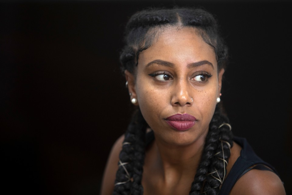In this Sunday, July 7, 2019 photo, Ethiopian Israeli musician Yael Mentesnot gives an interview to The Associated Press, in her house in Tel Aviv, Israel. A wave of Ethiopian Israeli artists have burst onto Israel's vibrant hip-hop scene, using the stage to promote their community's struggle against discrimination and police violence. (AP Photo/Sebastian Scheiner)