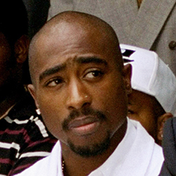 "In this Aug. 15, 1996, file photo, rapper Tupac Shakur attends a voter registration event in South Central Los Angeles. It was an odd couple: Records show that Iowa Department of Human Services Director Jerry Foxhoven had an unusually strong interest in the late Tupac Shakur during his two-year tenure, which abruptly ended last June 2019. He had weekly ""Tupac Fridays"" to play his music in the office, he traded Tupac lyrics with employees and he marked his own 65th birthday with Tupac-themed cookies, including ones decorated with the words ""Thug life."" (AP Photo/Frank Wiese, File)"