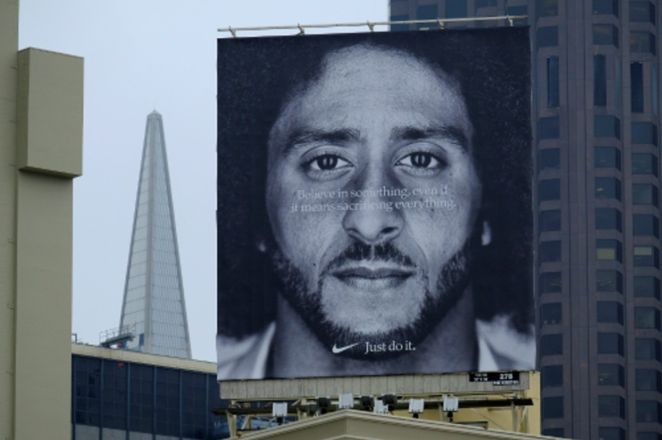 FILE - In this Sept. 5, 2018, file photo, a large billboard stands on top of a Nike store showing former San Francisco 49ers quarterback Colin Kaepernick, at Union Square in San Francisco. Nike is pulling a flag-themed tennis shoe after Kaepernick complained to the shoemaker, according to the Wall Street Journal. (AP Photo/Eric Risberg, File)