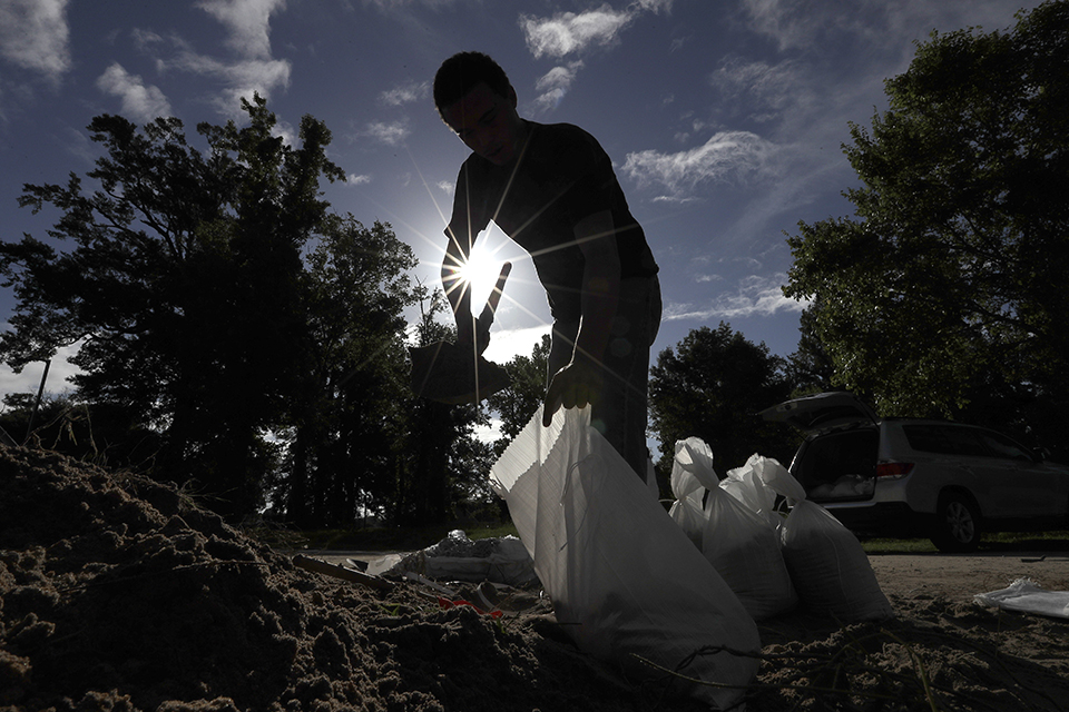 Chase Garces fills sandbags Friday, July 12, 2019, in Baton Rouge, La., ahead of Tropical Storm Barry. The National Weather Service in New Orleans says water is already starting to cover some low lying roads in coastal Louisiana as Barry approaches the state from the Gulf of Mexico. (AP Photo/David J. Phillip)
