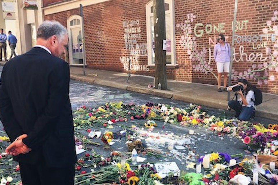 Tim Kaine inspects a makeshift memorial to Heather Heyer. Photo courtesy his office