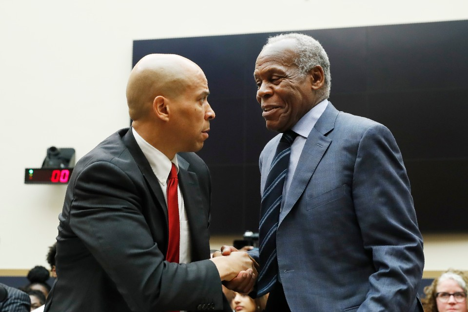 Democratic Presidential candidate Sen. Cory Booker, D-NJ, left, greets Actor Danny Glover, before they testify about reparations for the descendants of slaves, during a hearing before the House Judiciary Subcommittee on the Constitution, Civil Rights and Civil Liberties, at the Capitol in Washington, Wednesday, June 19, 2019. (AP Photo/Pablo Martinez Monsivais)