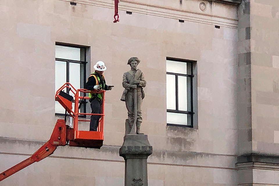 A workman prepares a Confederate staute for removal