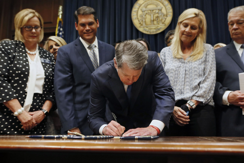 Georgia's Republican Gov. Brian Kemp, center, signs legislation in Atlanta, banning abortions once a fetal heartbeat can be detected, which can be as early as six weeks before many women know they're pregnant, May 7, 2019. Georgia became the fourth state to enact the ban on abortions after a fetal heartbeat can be detected. (Bob Andres/Atlanta Journal-Constitution via AP, File)