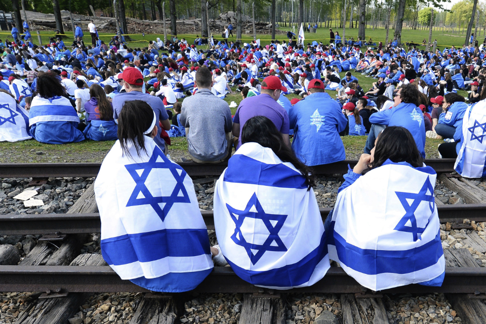 "Young Jews from around the world are draped with Israeli flags in the former Nazi German death camp of Birkenau during the annual Holocaust remembrance event, the ""March of the Living"" in memory of the six million Holocaust victims in Oswiecim, Poland, Thursday, May 2, 2019.(AP Photo/Czarek Sokolowski)"