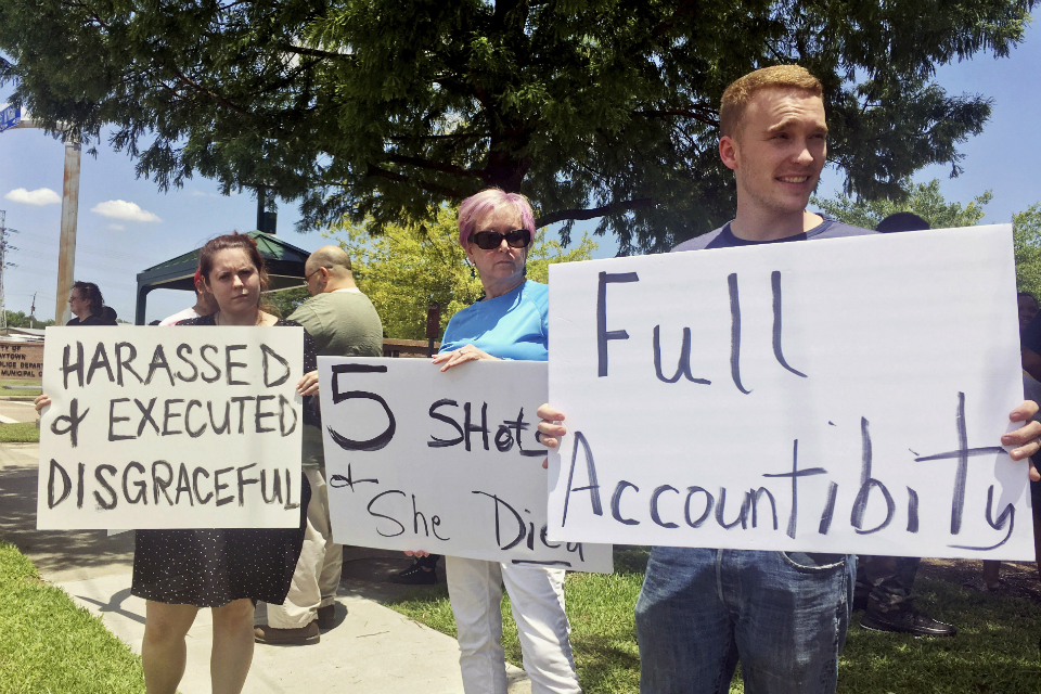 "From left, Felicia Young, 28, Susan Cummings, 61, and Bryon Cummings, 22, demonstrate outside Baytown Police Department in Baytown, Texas, Tuesday, May 14, 2019. A Texas police officer fatally shot a woman who police said grabbed his Taser and used it against him, moments after she seemed to say ""I'm pregnant"" in an altercation captured on video. (AP Photo/John L. Mone)"