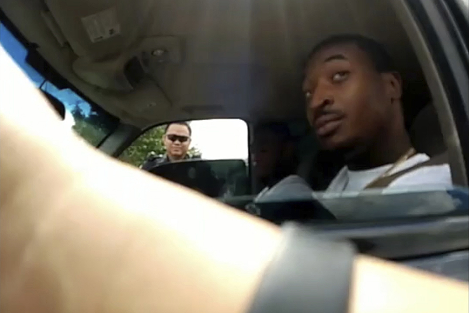 This file screenshot taken from Sept. 1, 2018, police body camera video provided by the Arlington, Texas, Police Department, shows an officer, foreground, talking to O'Shae Terry after stopping him for a vehicle registration violation, in Arlington, as a second officer, Bau Tran, background left, looks in from the passenger side window. Tran has been charged with criminally negligent homicide for fatally shooting Terry during the traffic stop. (Arlington Police Department via AP, File)