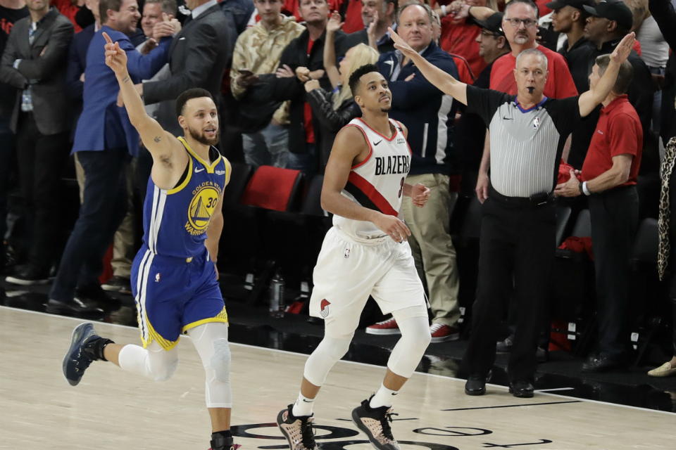 Golden State Warriors guard Stephen Curry, left, celebrates as he runs next to Portland Trail Blazers guard CJ McCollum, center, at the end of Game 4 of the NBA basketball playoffs Western Conference finals, Monday, May 20, 2019, in Portland, Ore. The Warriors won 119-117 in overtime. (AP Photo/Ted S. Warren)