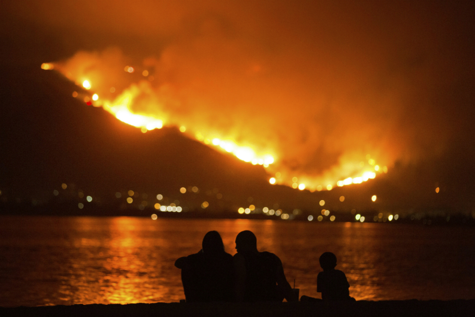 In this Aug. 9, 2018, file photo, a family sits along the shore of Lake Elsinore as they watch the Holy Fire burn in the distance in Lake Elsinore, Calif. The National Interagency Fire Center is predicting a heavy wildfire season for areas along the west coast of the United States this summer. The Boise, Idaho-based center said Wednesday, May 1, 2019, that most of the country can expect a normal wildfire season in the period from May through August. (AP Photo/Patrick Record, File)