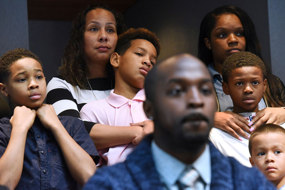 Marcus Riley of Bolingbrook, Ill., foreground, speaks during a press conference Tuesday, Nov. 5, 2019 in Aurora, Ill., about how he and other families, background, were asked to move because others didn't want to sit by them at a Naperville, Ill., Buffalo Wild Wings restaurant