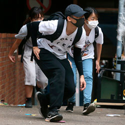People wearing face masks duck down as they walk at Hong Kong Polytechnic University in Hong Kong, Tuesday, Nov. 19, 2019