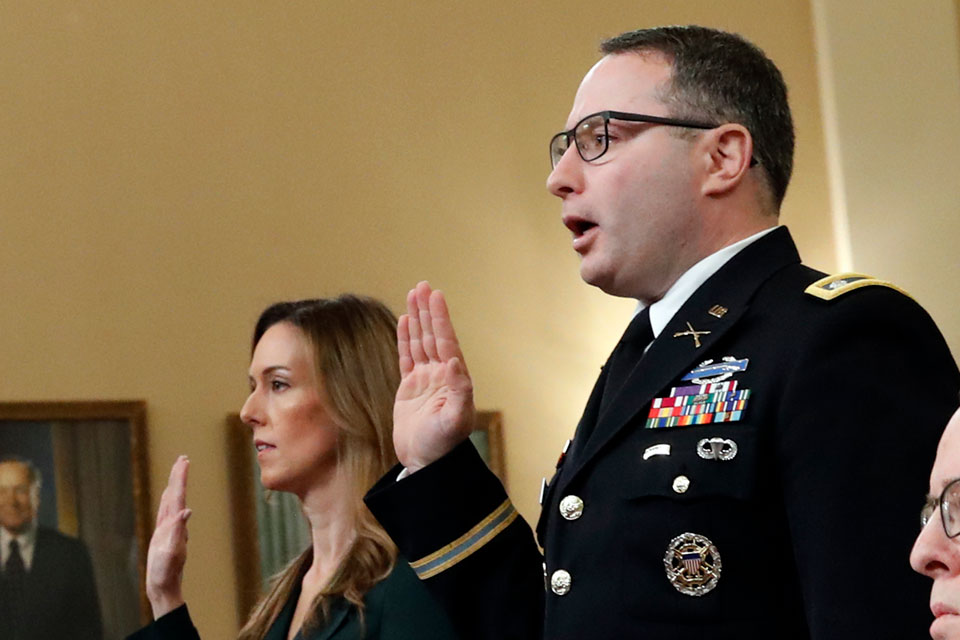 Jennifer Williams, an aide to Vice President Mike Pence, and National Security Council aide Lt. Col. Alexander Vindman, are sworn in before they testify before the House Intelligence Committee on Capitol Hill in Washington, Tuesday, Nov. 19, 2019, during a public impeachment hearing of President Donald Trump's efforts to tie U.S. aid for Ukraine to investigations of his political opponents
