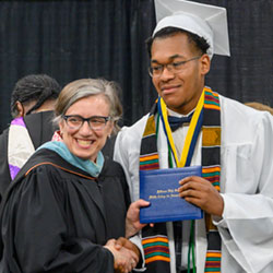 Jefferson High principal Margaret Calvert poses for a photo with a graduate. (photo courtesy PPS)
