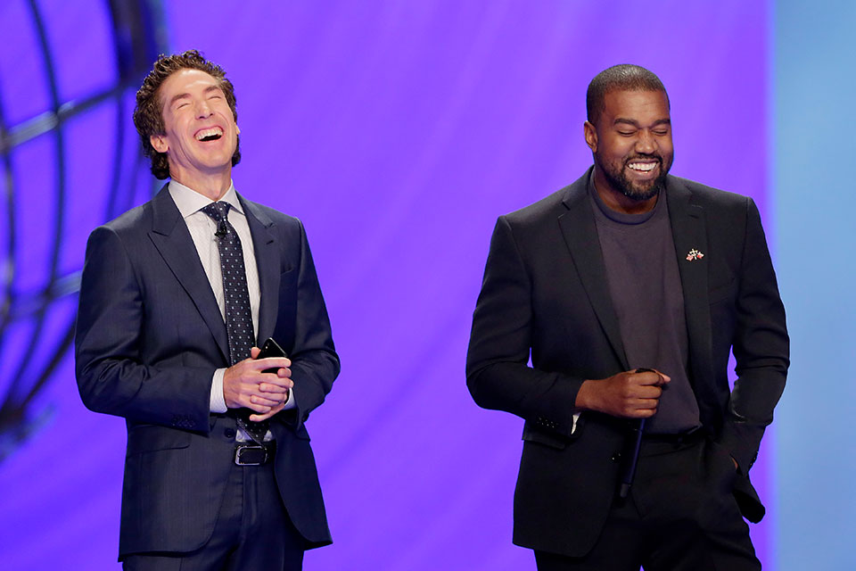 With their eyes closed for prayer, Joel Osteen, left, and Kanye West laugh as West makes a joke while leading the prayer during a service at Lakewood Church, Sunday, Nov. 17, 2019, in Houston