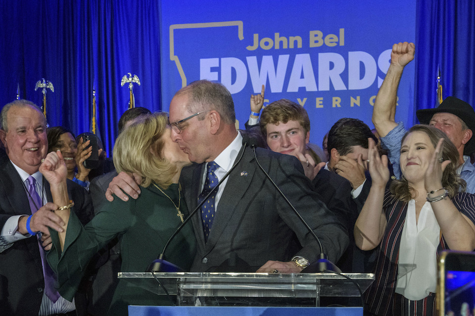 Louisiana Gov. John Bel Edwards celebrates with his wife Donna Edwards as he arrives to address supporters at his election night watch party in Baton Rouge, La., Saturday, Nov. 16, 2019. (AP Photo/Matthew Hinton)