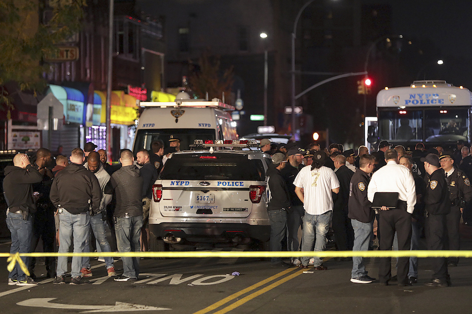 Oct. 25, 2019 file photo, New York police and other emergency personnel investigate the scene of a shooting at a nail salon in the Brownsville neighborhood of the Brooklyn borough of New York. Police say the man who attacked a police officer with a metal chair was shot to death by the officer. A surge in violent police clashes in recent weeks has left a trail of bodies across the city and stoked tensions between officers and critics who say they have been too quick to use deadly force. (AP Photo/Julius Motal, File)