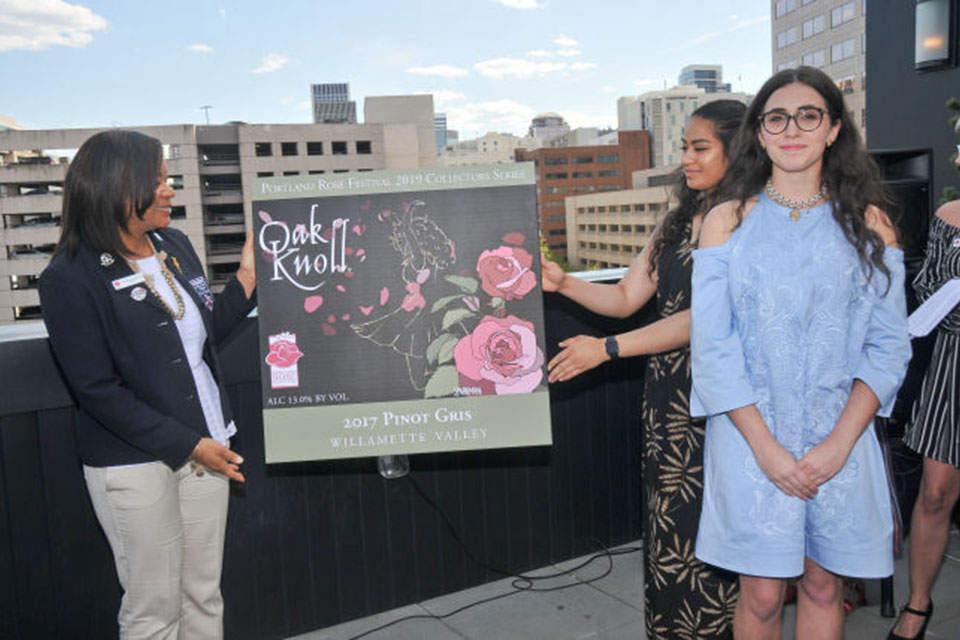 Artist Caitlyn Sparkman (in blue) standing next to her 2019 winning label held by Rose Festival Foundation President Teri Bowles-Atherton