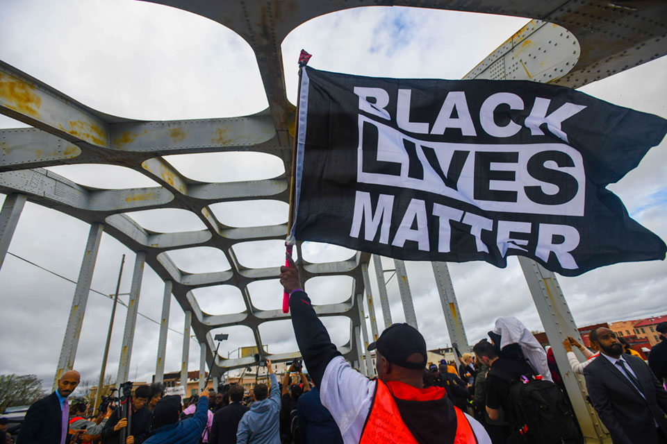 Black Lives Matter demonstrator waves a flag on the Edmund Pettus Bridge during the Bloody Sunday commemoration in Selma, Ala.