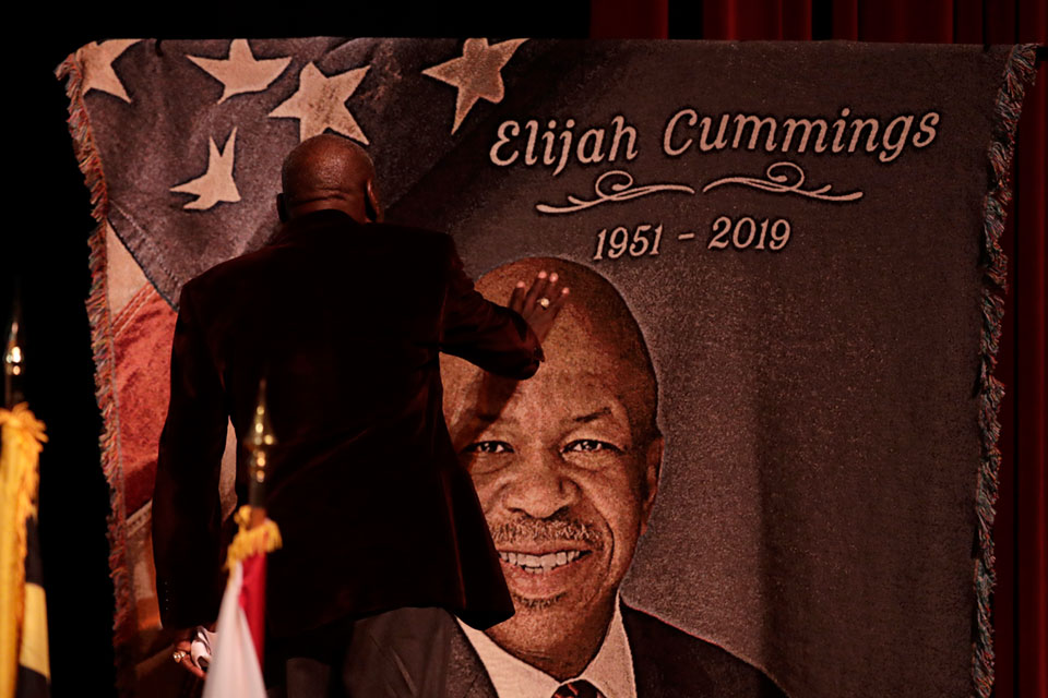 Norris Davis, friend of the late U.S. Rep. Elijah Cummings, touches a banner with the likeness of the congressman