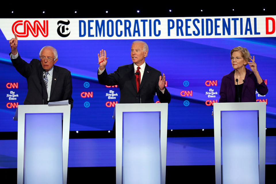 Democratic presidential candidate Sen. Bernie Sanders, I-Vt., left, former Vice President Joe Biden, center, and Sen. Elizabeth Warren, D-Mass., raise their hands to speak during a Democratic presidential primary debate