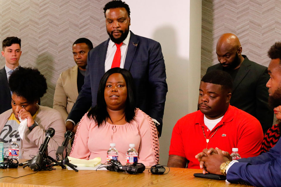 Amber Carr, left, wipes a tear as her sister Ashley Carr, center, talks about their sister, Atatiana Jefferson, as their brother, Adarius Carr, right and attorney Lee Merritt, standing, listen during a news conference Monday, Oct. 14, 2019 in downtown Dallas. The family of the 28-year-old black woman who was shot and killed by a white police officer in her Fort Worth home