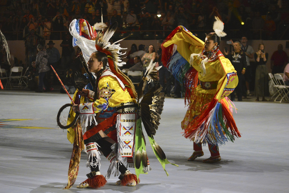 Dancers enter at the Gathering of Nations, one of the world's largest gatherings of indigenous people in Albuquerque, N.M., April 27, 2019. A handful of states, including New Mexico and Maine, are celebrating their first Indigenous Peoples' Day as part of a trend to move away from a day honoring Christopher Columbus. (AP Photo/Russell Contreras, File)
