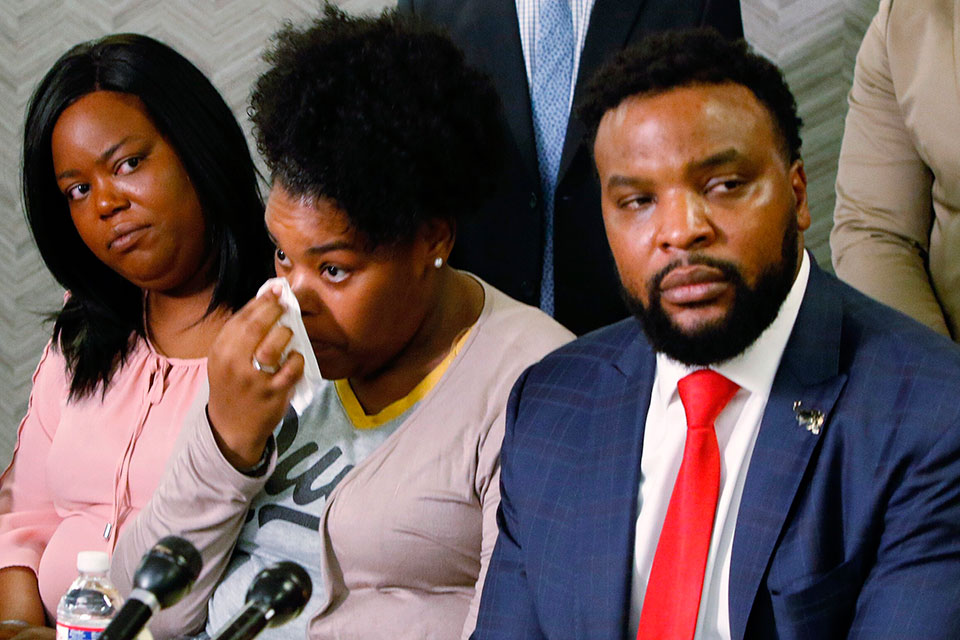Amber Carr, center, wipes a tear as her sister, Ashley Carr, left, and attorney Lee Merritt, right, listen to their brother Adarius Carr talk about their sister, Atatiana Jefferson