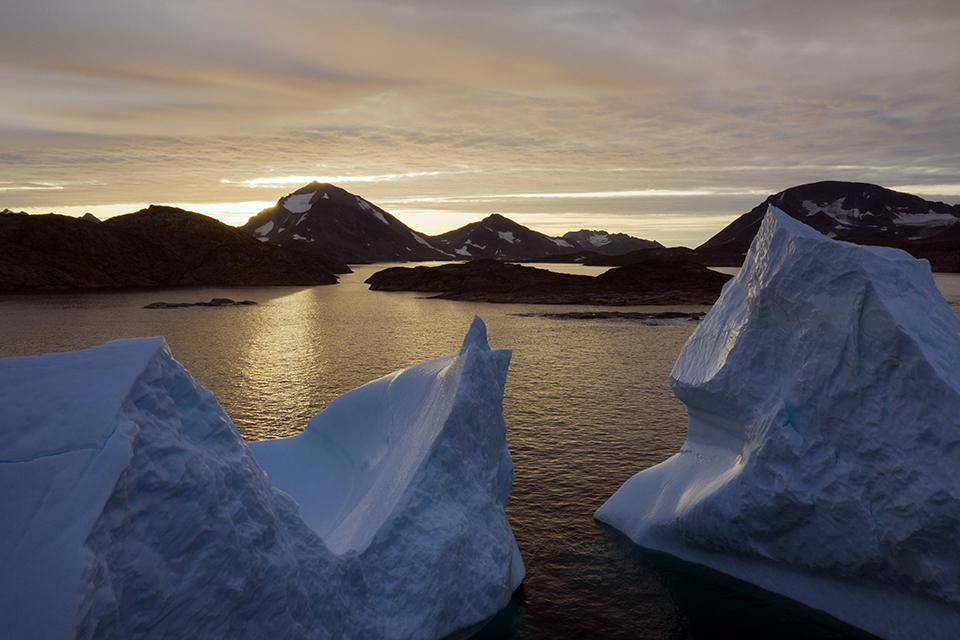 This early Friday, Aug. 16, 2019 file photo shows an aerial view of large icebergs floating as the sun rises near Kulusuk, Greenland. Greenland has been melting faster in the last decade, and this summer, it has seen two of the biggest melts on record since 2012. A special United Nations-affiliated oceans and ice report released on Wednesday, Sept. 24, 2019 projects three feet of rising seas by the end of the century, much fewer fish, weakening ocean currents, even less snow and ice, and nastier hurricanes, caused by climate change. (AP Photo/Felipe Dana)
