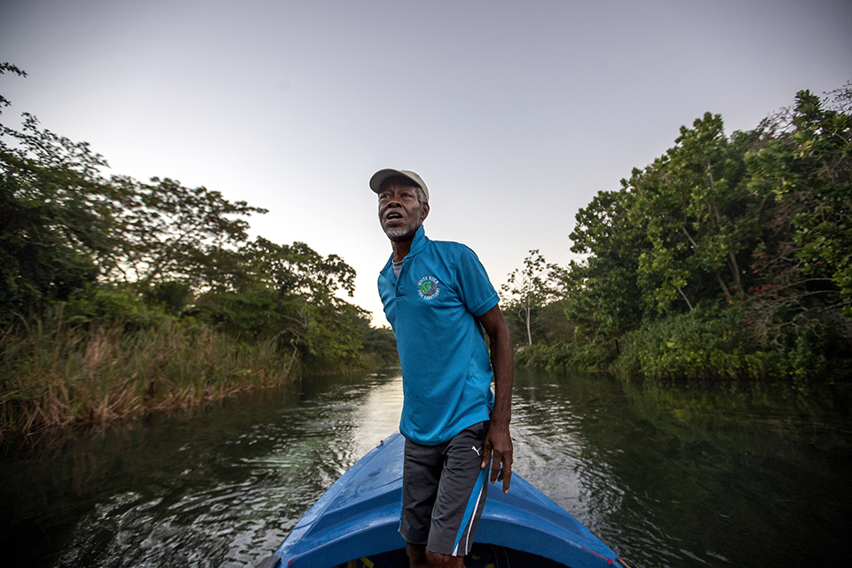 "White River Fish Sanctuary warden and diver Everton Simpson heads out to sea to patrol against illegal fishing at dawn in White River, Jamaica, Tuesday, Feb. 12, 2019. Once a spear fisherman and later a scuba-diving instructor, Simpson started working as a ""coral gardener"" and warden two years ago, part of grassroots efforts to bring Jamaica's coral reefs back from the brink. (AP Photo/David Goldman)"