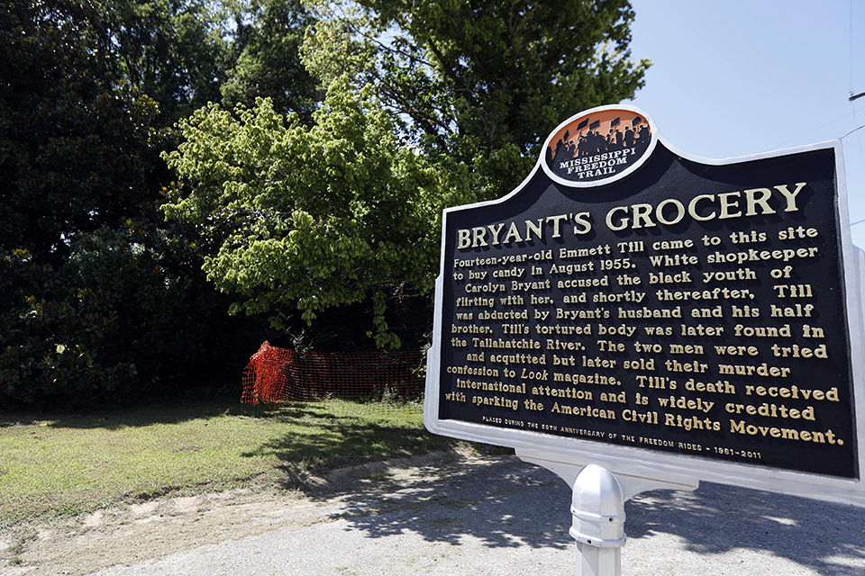 In this July 12, 2018 file photo, a Mississippi Freedom Trail marker recaps the significance of Bryant's Grocery and Meat Market, left, now in ruins, in Money, Miss., where in 1955, 14-year old Emmett Till, an African American male, allegedly whistled, grabbed and made sexual advances to Carolyn Bryant, a white woman, then wife of the store's owner. The federal government is still investigating the brutal slaying of Till, whose death helped spur the civil rights movement 60 years ago. A Justice Department report issued to Congress about civil rights cold case investigations lists Till's killing as being among the unit's active cases. (AP Photo/Rogelio V. Solis, File)