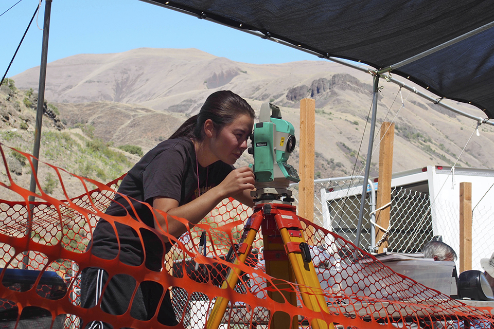 This 2015 photo provided by Loren Davis shows a researcher taking measurements at the Cooper's Ferry canyon archaeological site in western Idaho. In a report released on Thursday, Aug. 29, 2019, scientists say they've found artifacts that indicate people were living here around 16,000 years ago, providing new evidence that the first Americans entered their new home by following the Pacific Coast. (Loren Davis via AP)