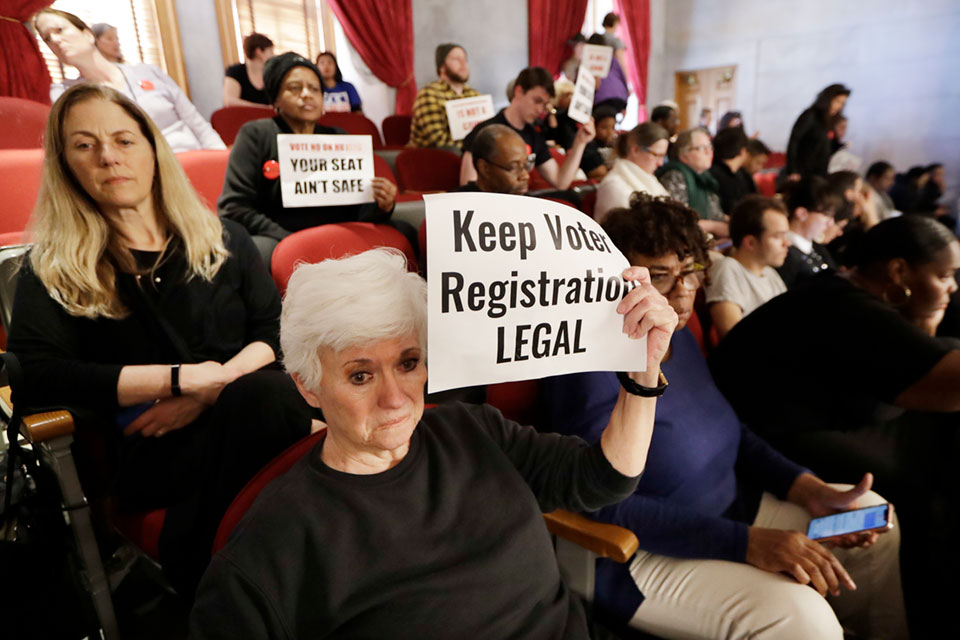Suzanne Lanier, front left, holds up a sign in the House gallery as she and others oppose a bill pushed by the Tennessee Secretary of State that would impose new restrictions on groups that hold voter registration drives