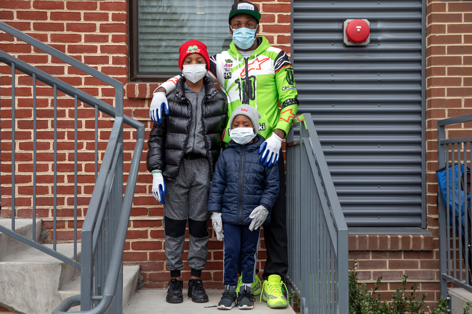 In this March 31, 2020, photo, ManPower DC founder and CEO Jimmie Jenkins, 30, poses for a photograph with his sons, Jahrei Montgomery, 11, and Ashton Cross, 5, outside their home in Washington. Since mid-March Jenkins has had his children wear protective masks and gloves anytime they leave the house. Jenkins is part of a community food outreach initiative, in partnership with Martha's Table, to get needed food directly to neighborhoods in southeast Washington. Local volunteers are the tip of the spear for a grassroots community effort to keep Washington's most vulnerable neighborhoods fed during the unprecedented coronavirus crisis which has nearly shut down the American economy. (AP Photo/Jacquelyn Martin)