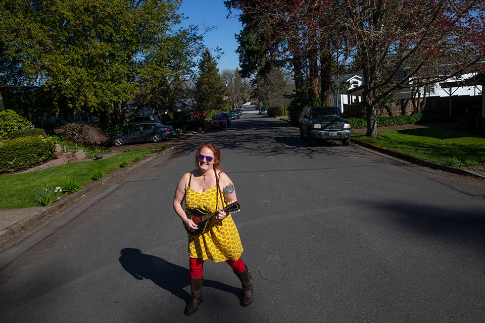Elizabeth Cable plays music to cheer her neighbors during a walk in Eugene, Ore., on Saturday, March 21, 2020 in the midst of a voluntary plea by officials to social distance from others in an effort to help limit the spread of COVID-19.