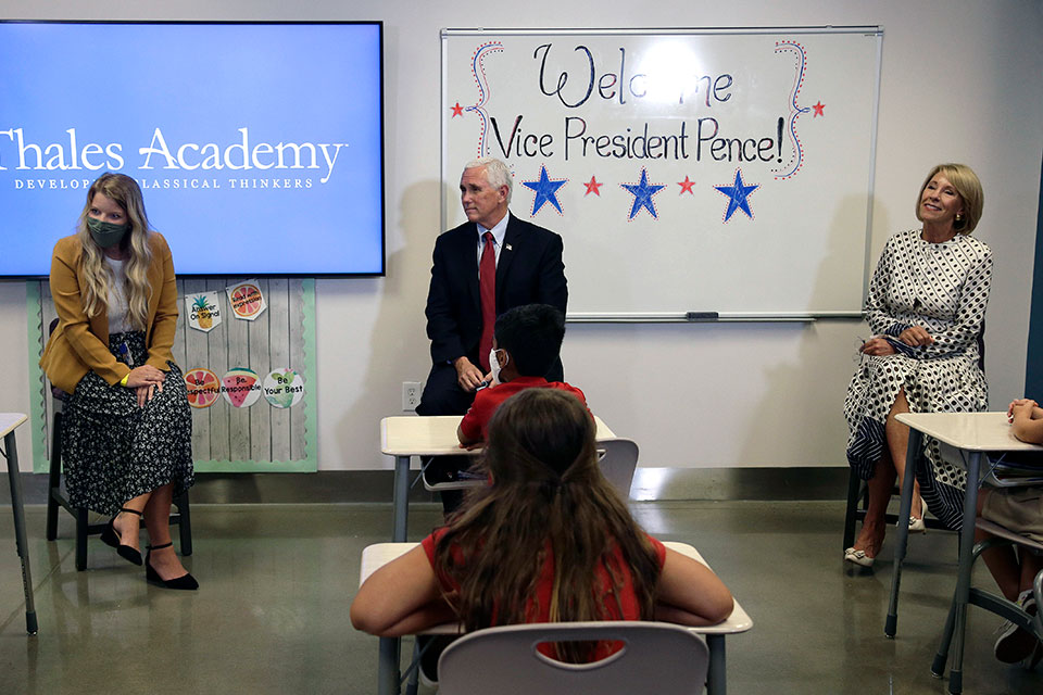 Vice President Mike Pence and Education Secretary Betsy DeVos, right, visit with teacher Allison Combs, left, and her fourth grade students at Thales Academy, which reopened to students in Apex, N.C., Wednesday, July 29, 2020. (AP Photo/Gerry Broome)