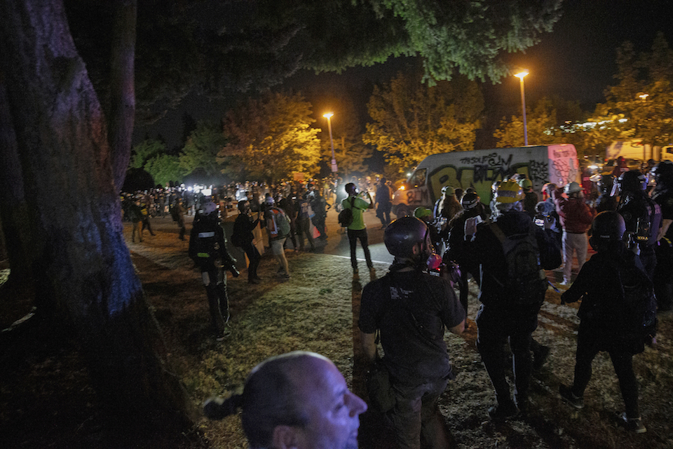 Demonstrators gather at Floyd Light City Park Thursday, Aug. 6, 2020 in Portland, Ore. Protests turned violent again even after the mayor pleaded with demonstrators to stay off the streets. Police say an officer suffered what was described as a severe injury after being hit with a rock late Thursday. (Mark Graves /The Oregonian via AP)