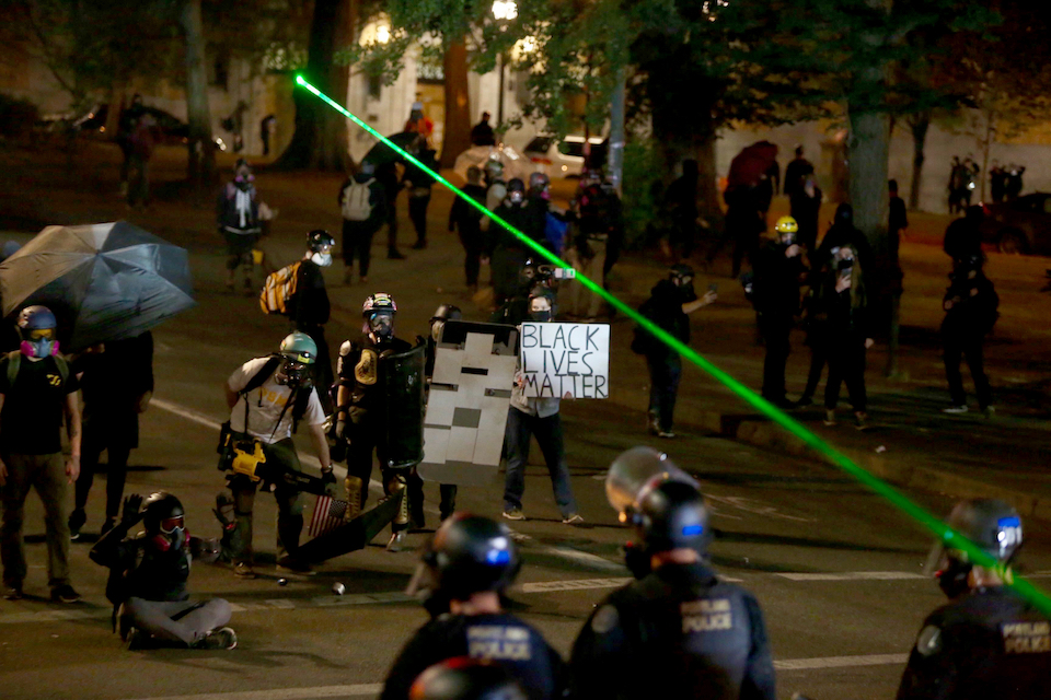 Police and protesters clash during a demonstration, early Thursday, Aug. 13, 2020, in downtown Portland. Protests have been held nightly in the city since the police killing of George Floyd in May, who died after a white officer pressed a knee to his neck in Minneapolis. (Sean Meagher/The Oregonian via AP)