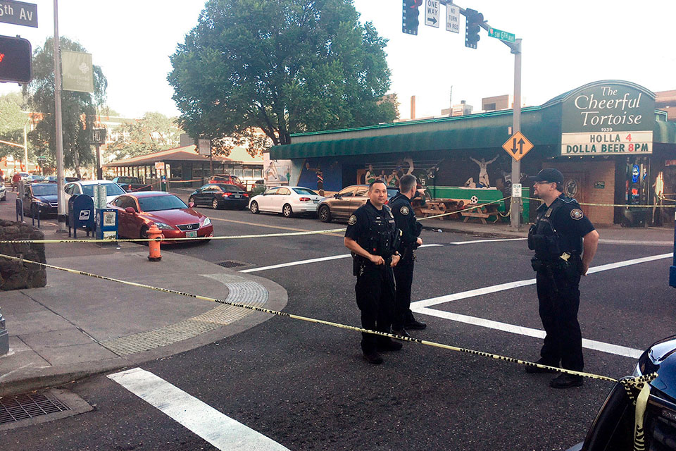 In this June 29, 2018, file photo, police stand outside across from The Cheerful Tortoise bar at the scene of an earlier shooting in Portland, Ore. Portland State University said Thursday, Aug. 13, 2020, it will disarm its campus police force more than two years after officers from the department shot and killed a Black man who was trying to break up a fight. (Shane Dixon/The Oregonian via AP, File)