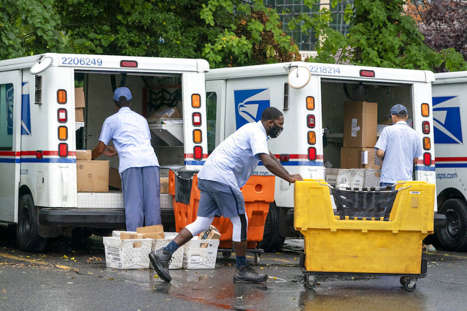 Letter carriers load mail trucks for deliveries at a U.S. Postal Service facility in McLean, Va., July 31, 2020. The success of the 2020 presidential election could come down to a most unlikely government agency: the U.S. Postal Service. (AP Photo/J. Scott Applewhite, File)