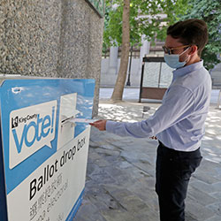 A person drops off a ballot for Washington state's primary election Tuesday, Aug. 4, 2020, at a collection box at the King County Administration Building in Seattle.