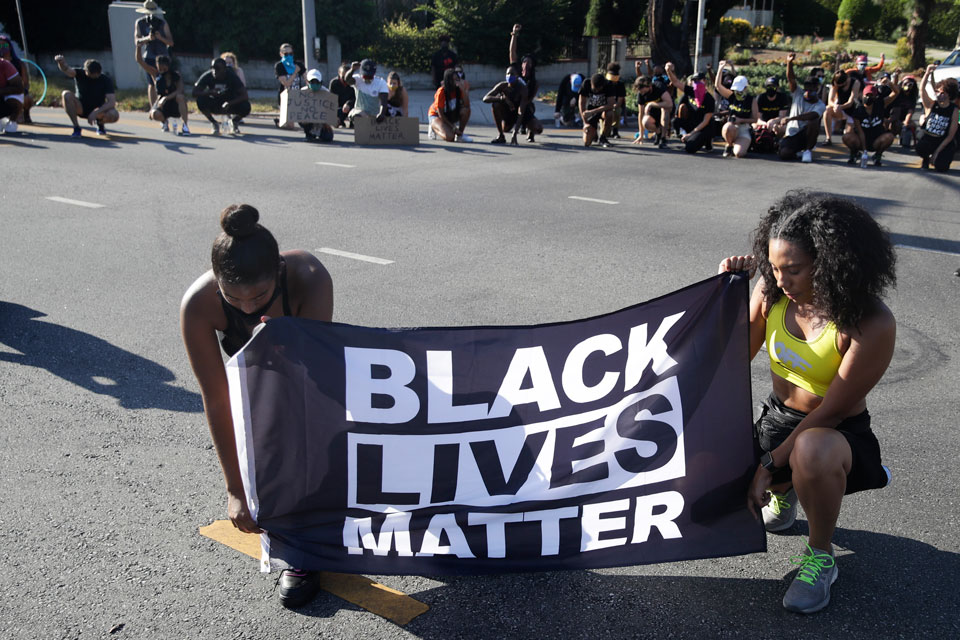 In this July 11, 2020 file photo, Alycia Pascual-Pena, left, and Marley Ralph kneel while holding a Black Lives Matter banner during a protest in memory of Breonna Taylor, in Los Angeles. Taylor was killed in her apartment by members of the Louisville, Ky., Metro Police Department on March 13. The International Law Enforcement Educators and Trainers Association, a prominent law enforcement training group, is promoting a lengthy research document riddled with falsehoods and conspiracies that urges local police to treat Black Lives Matter activists as terrorists plotting a violent revolution. The document contains misinformation and inflammatory rhetoric that could incite officers against protesters and people of color, critics said. (AP Photo/Marcio Jose Sanchez, File)