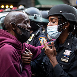 In this June 2, 2020 file photo, a protester and a police officer shake hands in the middle of a standoff at a rally in New York, calling for justice over the death of George Floyd, a Black man who died under the knee of a white police officer in Minneapolis on May 25.