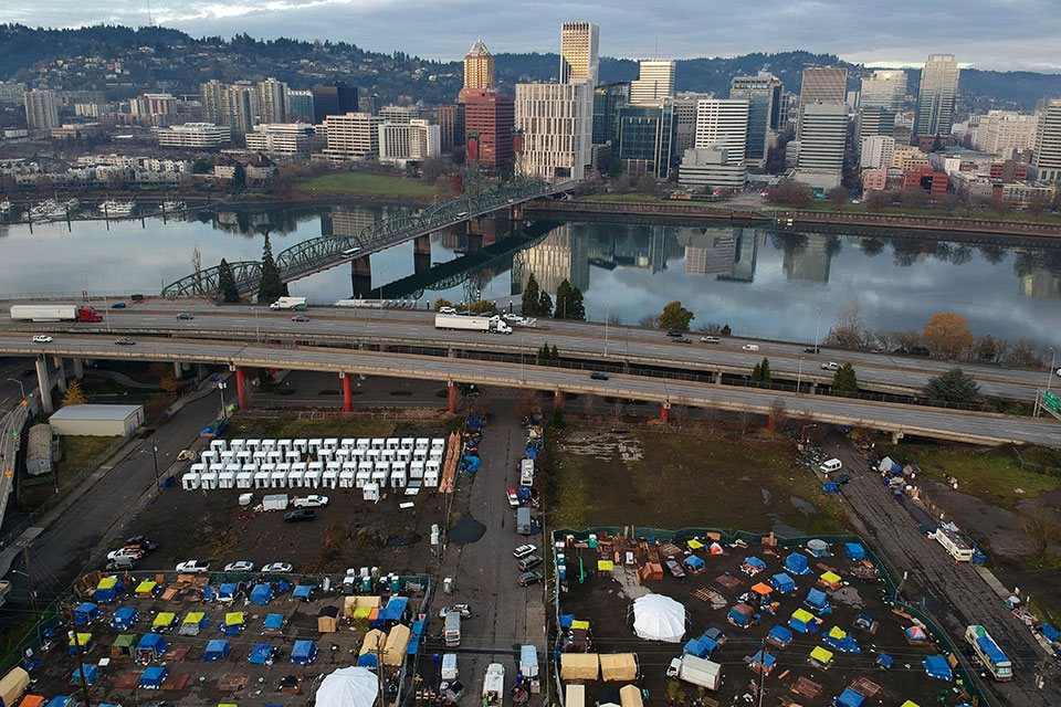 "In this aerial photo taken with a drone, homeless camps are seen in a vacant parking lot on the central eastside in Portland, Ore., Tuesday, Dec. 8, 2020. Portland this month assembled neat rows of the shelters, center left, which resemble garden sheds, in three ad-hoc ""villages"", part of an unprecedented effort unfolding in cold-weather cities nationwide to keep people without permanent homes safe as temperatures drop and coronavirus cases surge. (AP Photo/Craig Mitchelldyer)"