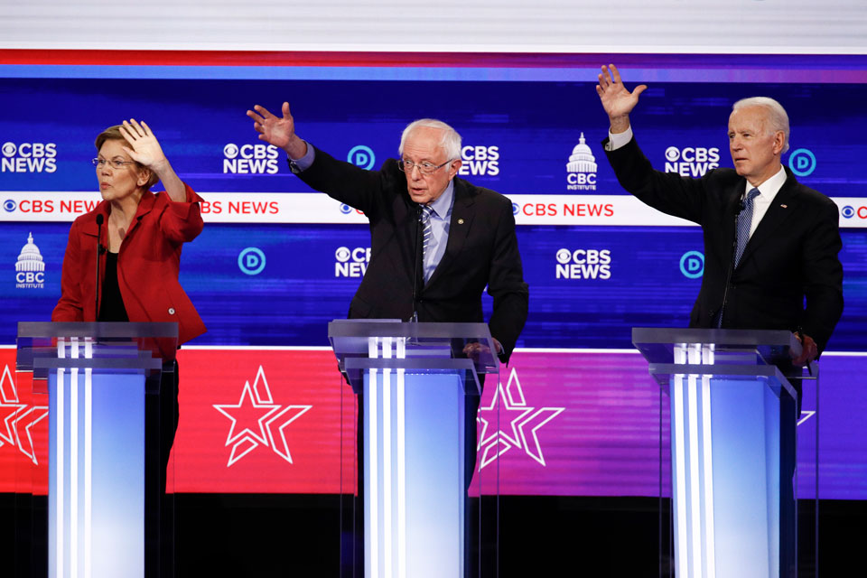 From left, Democratic presidential candidates, Sen. Elizabeth Warren, D-Mass., Sen. Bernie Sanders, I-Vt., and former Vice President Joe Biden, raises their hands as they participate in a Democratic presidential primary debate at the Gaillard Center, Tuesday, Feb. 25, 2020, in Charleston, S.C., co-hosted by CBS News and the Congressional Black Caucus Institute