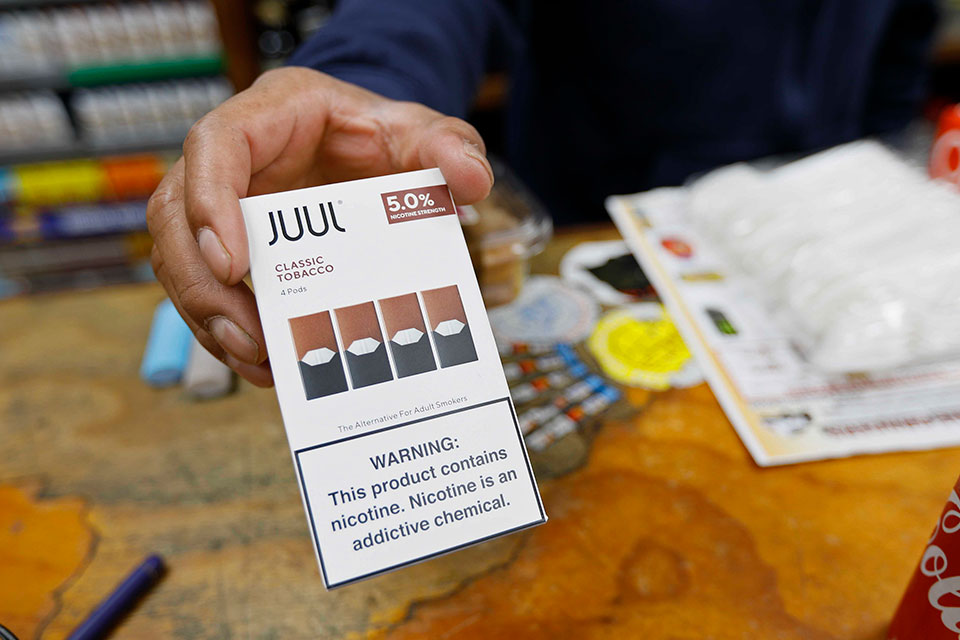 In this June 17, 2019, file photo, a cashier displays a packet of tobacco-flavored Juul pods at a store in San Francisco. Investigators from 39 states will look into the marketing and sales of vaping products by Juul Labs, including whether the company targeted youths and made misleading claims about nicotine content in its devices, officials announced Tuesday, Feb. 25, 2020. Juul released a statement saying it has halted television, print and digital advertising and eliminated most flavors in response to concerns by government officials and others.